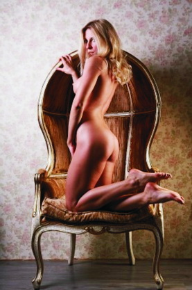 VIP escort Istanbul young blonde woman sits in a chair and shows long slim legs; an attractive woman with blond hair is naked in a chair looking at the camera and entices men to meet her