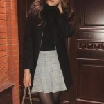 Escort agency Russia gal stands in the outerwear on the street and holds a purse