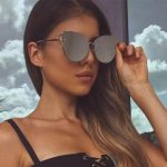 Istanbul escort girl Lina holds her stylish sunglasses with a reflective surface