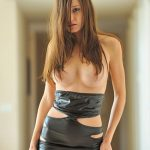 VIP escort bayan girl is standing in a big room with naked breasts without anything else but leather