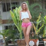 Incall escort agency girl stands in a big green garden showing her slim curvature