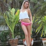 Incall escort agency girl is playing with her pants, pulling a part of them down