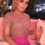 Call girl in Istanbul is sitting in some glamorous nightclub, wearing pink and drinking a pink cocktail