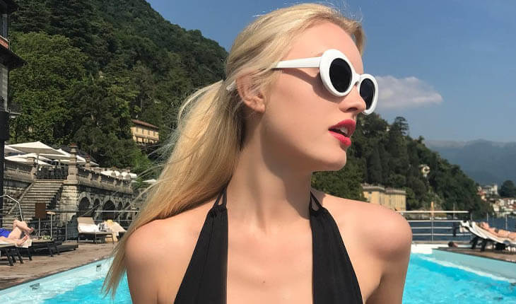 Escort Istanbul girl is at the beach or in a pool area wearing black-and-white sunglasses