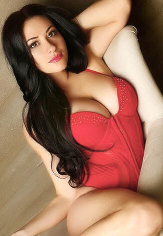 All escort girl is in the bed wearing luxuriant red body wear and looking at you with interest