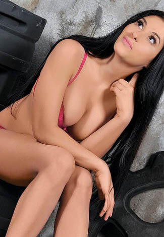 All escort girl gives a light smile wearing a little clothing and sitting on some metal thing