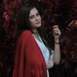 Escort Istanbul girl is standing near some wall of withered red leaves and wearing red shoulder cover
