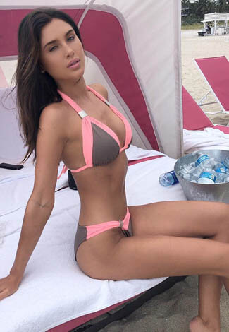 Incall escort Istanbul young woman is sitting on a beach couch demonstrating her total slimness