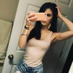 Istanbul escort girl demonstrates her litheness and wears a beige top and jean shorts