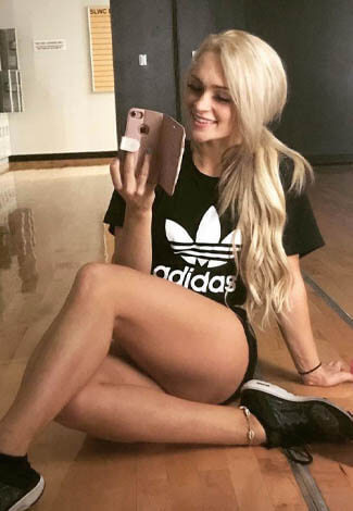 Escort girl is taking a selfie wearing an Adidas t-shirt, black shorts, and black-and-white sneakers