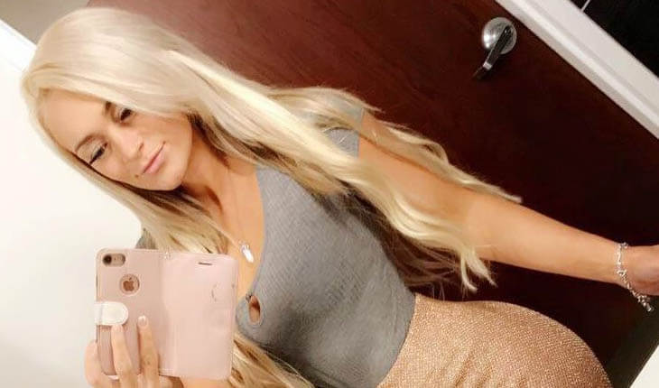 Escort girl does another selfie in a mirror, wearing a gray furry top & a golden skirt underlying shapes