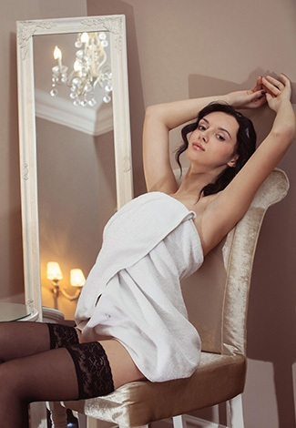 Escort Istanbul English girl is sitting on a bed with bare breasts – she almost took off her corset