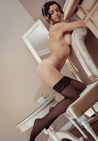 Istanbul call girl kneels in a seductive pose; her slim legs are in thin black stockings