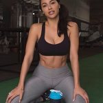 Escort services in Istanbul girl is sitting in a gym posing with two fitness products in front of her