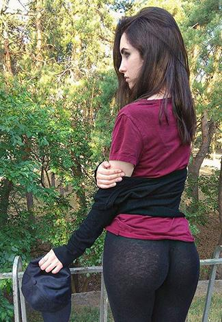 VIP escort Istanbul girl is standing at the midst of a bridge showing her buttocks in black leggings
