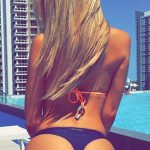 VIP escort girl shows her blond hair, which falls down on her spine, which ends with round arse