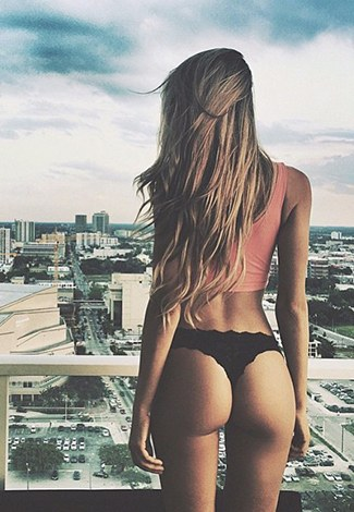 VIP escort girl is in the background of a large city, exposing her horny buttocks in black panties