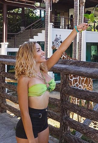 Girl for sex in Istanbul is feeding a giraffe in a zoo, smiling with a very wide appealing smile