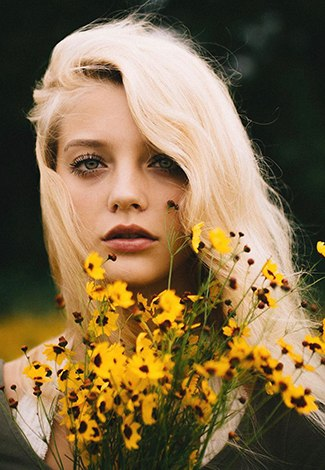 Escort girl Istanbul is holding a bunch of yellow wildflowers and slightly opens her mouth