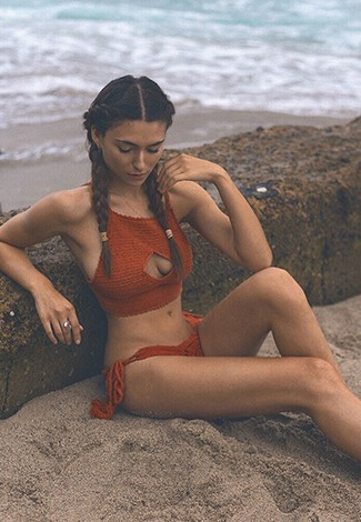 Istanbul luxury escort girl is on the sand looking down at her body, wearing red apparel