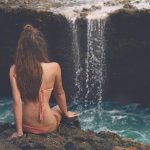 Istanbul luxury escort girl is sitting on the verge of a waterfall on the rocks, looking at flowing water