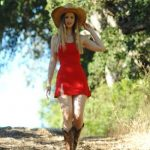 Beautiful dominant woman wears a red dress and takes a stroll on a country road wearing a hat