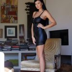 Mistress escort shows the fleshiness of her body by standing her side to the camera in a large room