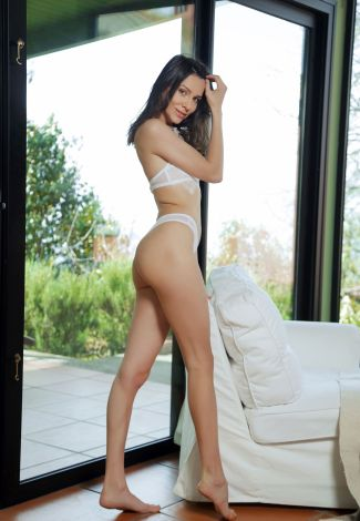 Istanbul escort 18 is standing close to a large panoramic door, which's leading to a garden