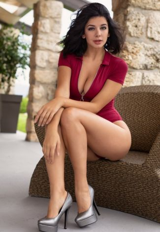 Istanbul VIP bayan escort lover of 23 y.o. is sitting on a cane-chair wearing red skintight apparel