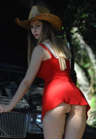 Beautiful dominant woman exposes her panties between the butt cheeks standing by a car