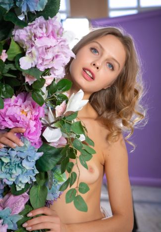 Lady bbw is hiding behind a flower bunch, which contains flowers of different sizes and colors