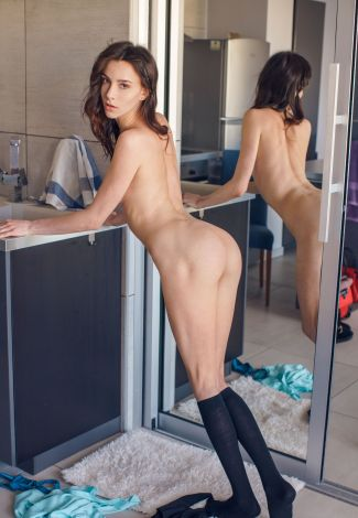 Western escorts mistress is standing completely naked leaning on the table in a kitchen