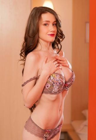 Ukranian escort in Turkey mistress touches her breasts above the bra, showing how big they are