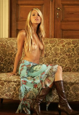 Escort agency Ukraine in Turkey girl is sitting on a couch with bare chest, partially covered
