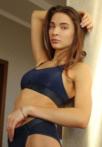 Busty Ukraine girl in Turkey is standing leaning against the wall, exhibiting her model look