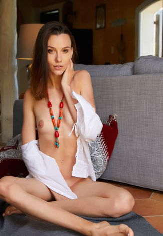 Russian elite escort pussycat is touching her cheek, representing a lovely-looking face & bare body