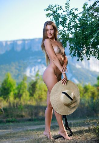 Busty milf escort girl has taken off her cloth, only holding a hat in hands, not interfering with nudity