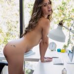 Russian outcall woman is completely naked, leaning against a working table and exposing her nudity